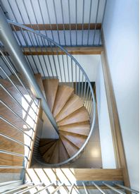 Domestic spiral staircase with oak treads and landing and matching powder coated stairwell balustrade