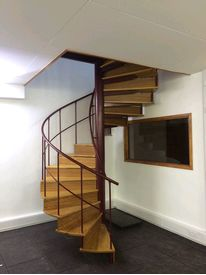 Powder coated spiral staircase with Iroko hardwood treads and risers in Fitzwilliam College,Cambridge