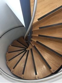 Spiral staircase with oak treads and stainless steel handrails