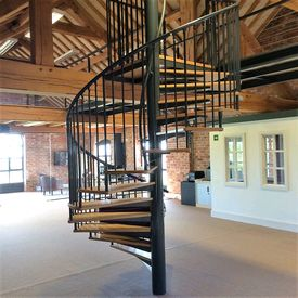 Spiral access staircase to office with oak treads and black powder coated paint finish