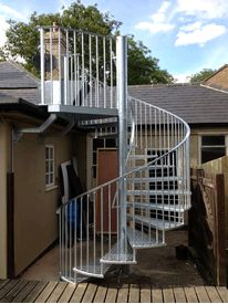 Galvanised spiral fire escape serving flat roof area to a Cambridge pub