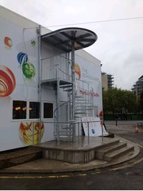 Galvanised access spiral staircase with weather canopy to marketing suite in Battersea