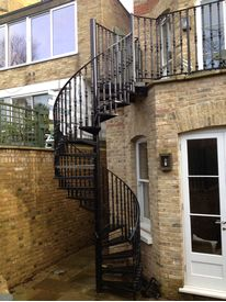 Powder coated domestic spiral staircase with decorative cast iron balustrade