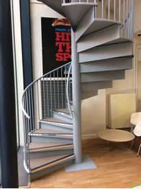 Steel treaded spiral staircase with rubber covers and contrasting nosings to Anglia Ruskin University cafe