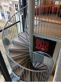 Spiral staircase giving access to a seated area within Anglia Ruskin University cafe