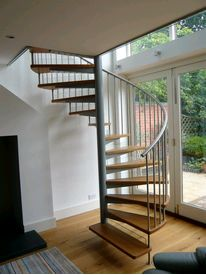 Domestic spiral staircase with clear glass risers,oak treads and stainless steel balustrades