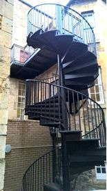 Double flight spiral fire escape with extended top landing platform at Stamford Town Hall